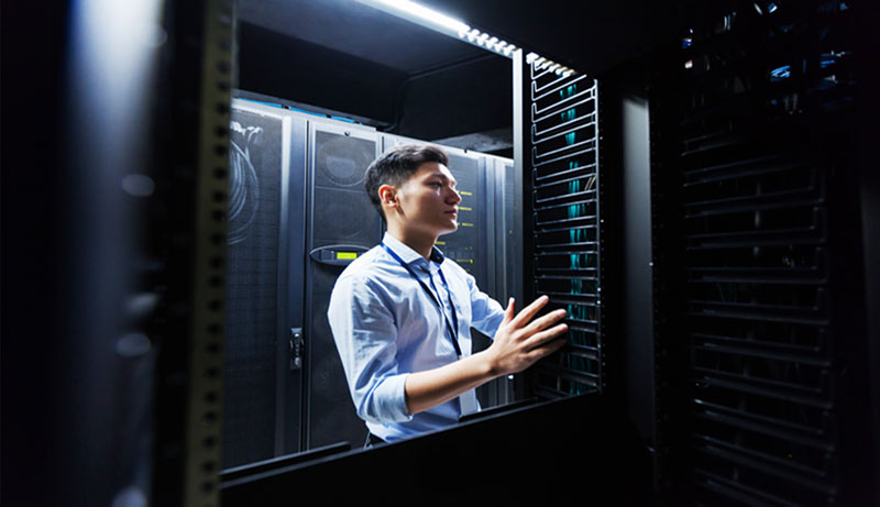 IT tech looking at servers in a data-center